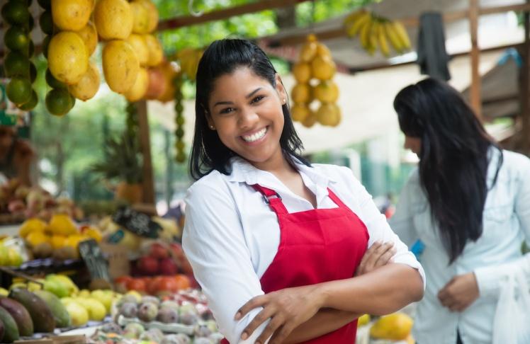 Lachende Obstverkäuferin auf dem Wochenmarkt